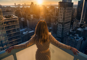 rich woman on balcony watching the sunset